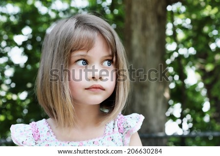 Cute little girl with bobbed hair cut looking away from camera. Extreme shallow depth of field. - stock photo