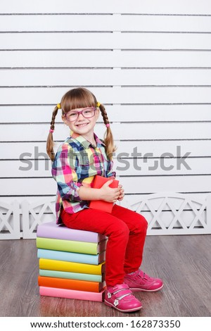 Cute little girl with books while wearing glasses, isolated over white - stock photo