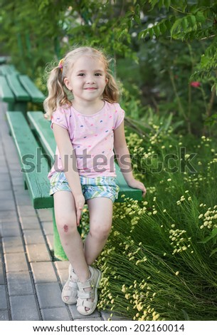 cute little girl with broken knees sitting on the bench