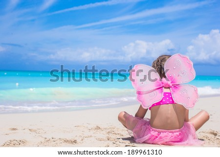 Cute little girl with butterfly wings on beach vacation - stock photo