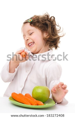 cute little girl with carrots and green apple, isolated over white - stock photo