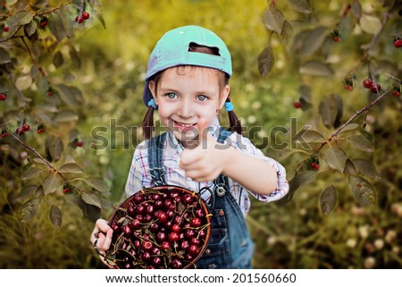 cute little girl with cherries showing her thumb up in the garden - stock photo