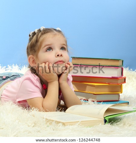 cute little girl with colorful books, on blue background - stock photo