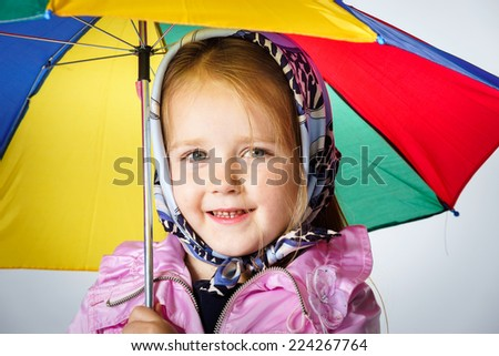 Cute little girl with colorful umbrella isolated on white background