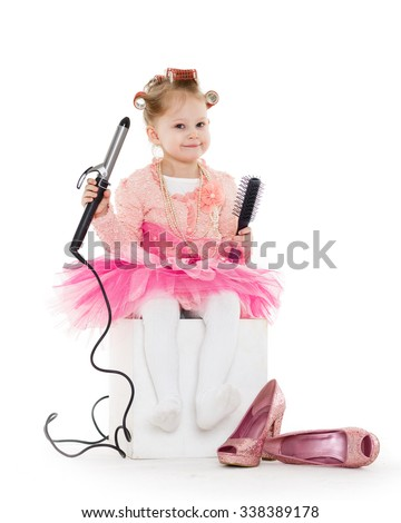 Cute little girl with curlers on her head dressed in pink clothes and a huge mother's shoes holds a curling iron on a white background. Little fashionista.  3 year old. - stock photo