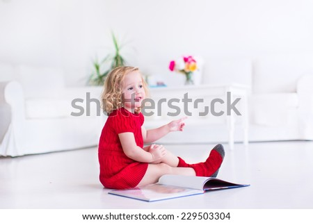 Cute little girl with curly hair wearing a warm knitted red dress and socks reading a book sitting on the floor in a white living room - stock photo