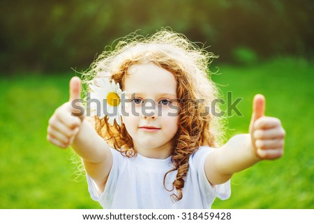 Cute little girl with daisy in her hairs, showing thumbs up in sunset light. - stock photo