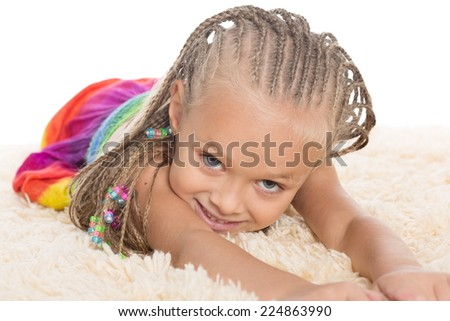Cute little girl with dreadlocks lays on the mat. Girl six years. - stock photo