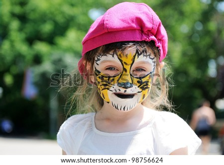 Cute little girl with face painted on a hot summer day - stock photo