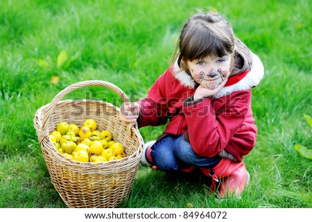 Cute little girl with face painted sitting outdoors with garden basket filled up with Japan quince - stock photo