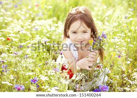 cute little girl with flowers in the summer field