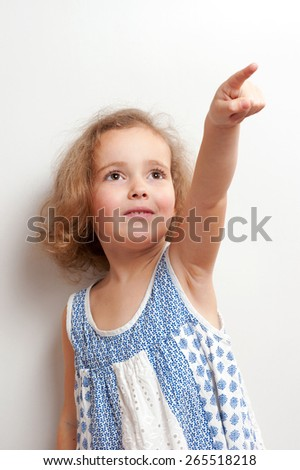 Cute little girl with funny ringlets (curly hair) in white and blue clothes looking very happy. She smiles, shows a hand with finger forward, looks ahead on a background white wall, studio portrait. - stock photo