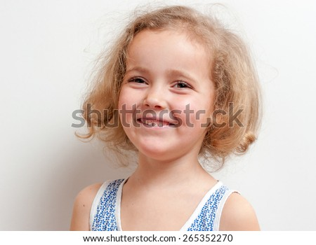 Cute little girl with funny ringlets (curly hair), looking very happy. She smiles and looks ahead on a background white wall, studio portrait. - stock photo