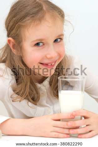 Cute little girl with glass of milk. - stock photo