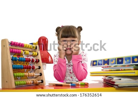 Cute little girl with glasses is drawing with felt-tip pen in preschool, best focus glasses, hair, shirt, soft focus device for computing, books, pens - stock photo