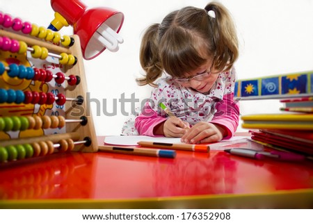 Cute little girl with glasses is drawing with felt-tip pen in preschool,best focus glasses, hair, shirt and pencil in hand, soft focus device for computing the pen on the table, books, hand - stock photo