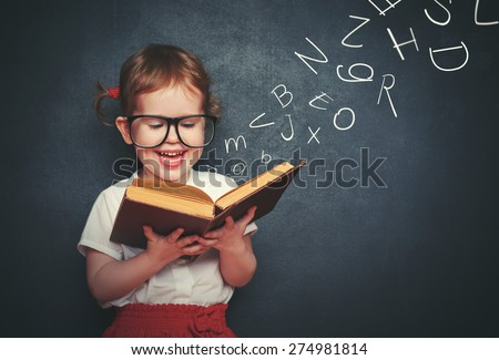 cute little girl with glasses reading a book with departing letters about Chalkboard - stock photo
