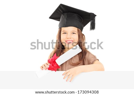 Cute little girl with graduation hat standing behind blank panel and holding a diploma isolated on white background - stock photo