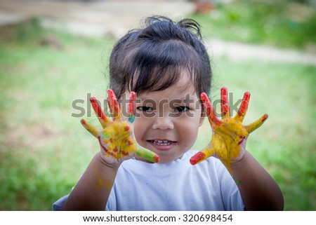Cute little girl with hands painted on green background - stock photo