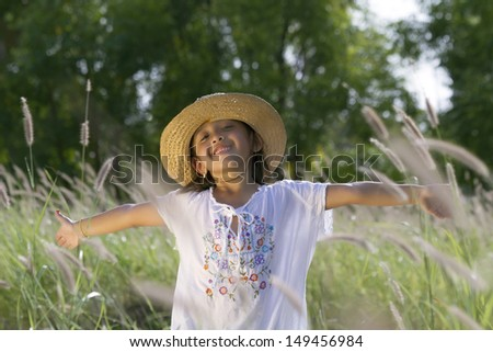 Cute little girl with hat smiles while having open arms in the countryside - stock photo