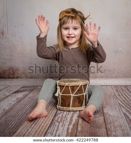 cute little girl with headband playing drum on the floor - stock photo