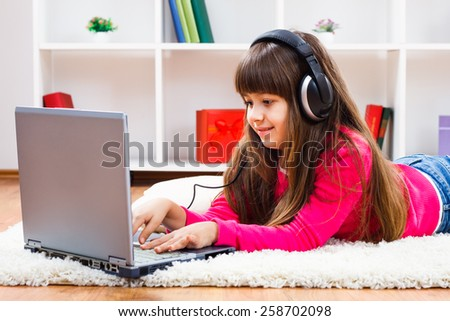 Cute little girl with headphones is using laptop at her home.Little girl with headphones using laptop - stock photo