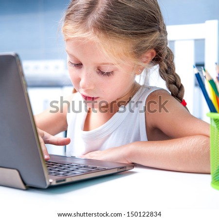 cute little girl with her computer at home at the table - stock photo