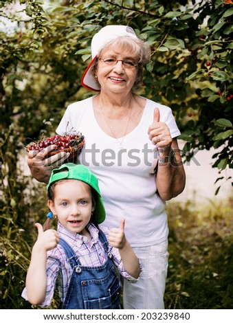 cute little girl with her grandmother holding cherries  showing  thumbs up in the garden - stock photo