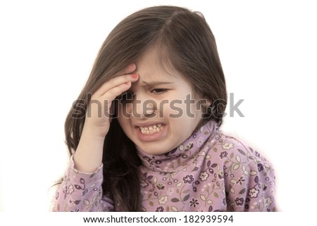 Cute little girl with her hand held to her forehead with painful expression showing headache - stock photo