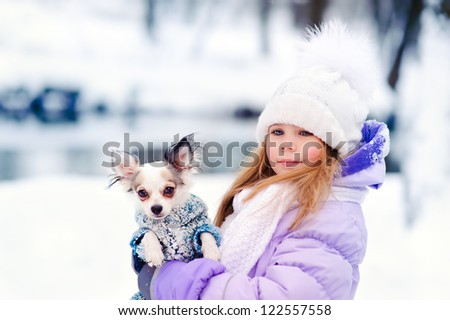 cute little girl with her lovely pets dog chihuahua in winter outdoor - stock photo