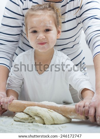 Cute little girl with her mother kneading dough at home.