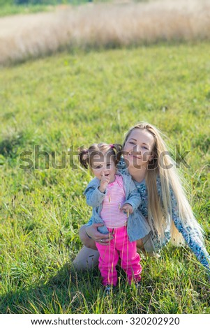Cute little girl with her mother playing together outdoors in the park