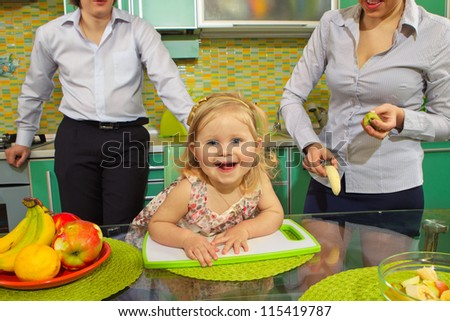Cute little girl with her parents in kitchen