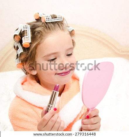 Cute little girl with lipstick and mirror and hair curlers - stock photo
