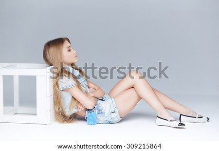 Cute little girl with long blond hair posing on the floor in studio. - stock photo
