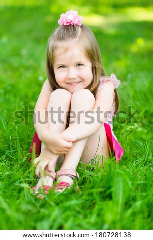 Cute little girl with long blond hair, sitting on grass in summer park putting her hands around her legs, outdoor portrait - stock photo