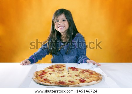 Cute little girl with long hair has blue sweater cheerful expression in front of a pizza - stock photo