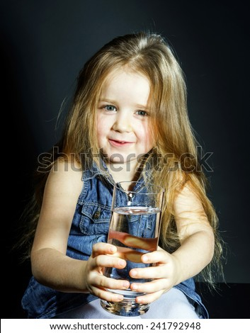 Cute little girl with long hair holding transparent glass with clear water - stock photo