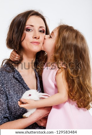 Cute little girl with long hair kissing her mom - stock photo