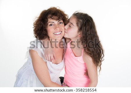Cute little girl with long hair kissing her mom isolated on white - stock photo