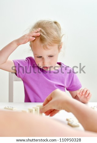 Cute little girl with mother playing domino at the table