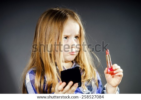 Cute little girl with mother's cosmetics, close-up portrait, isolated on dark background - stock photo