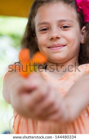Cute little girl with orange lilly flower in her hands
