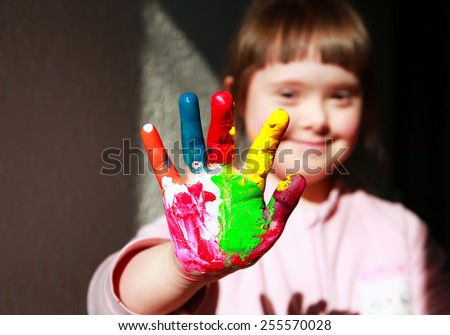 Cute little girl with painted hand - stock photo
