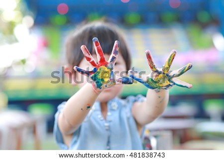 Cute little girl with painted hands, selective focus on hand