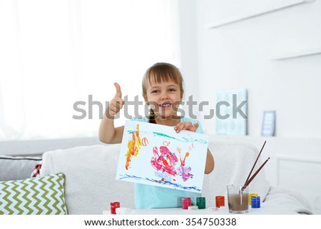 Cute little girl  with picture on home interior background