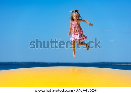 Cute little girl with pigtail jumping on an inflatable trampoline at the beach.