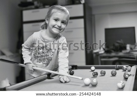 Cute little girl with pigtails playing pool in the billiard hall - stock photo