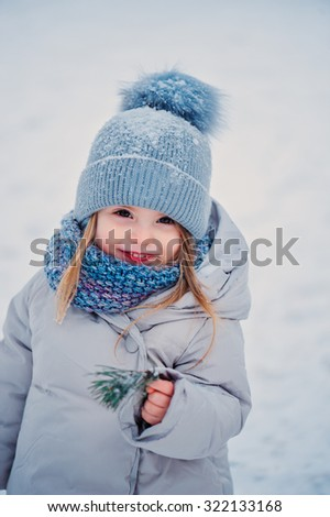 cute little girl with pine branch in grey coat and knitted blue scarf and hat on the winter walk - stock photo