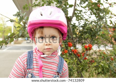 Cute little girl with pink bicycle helmet outdoors
